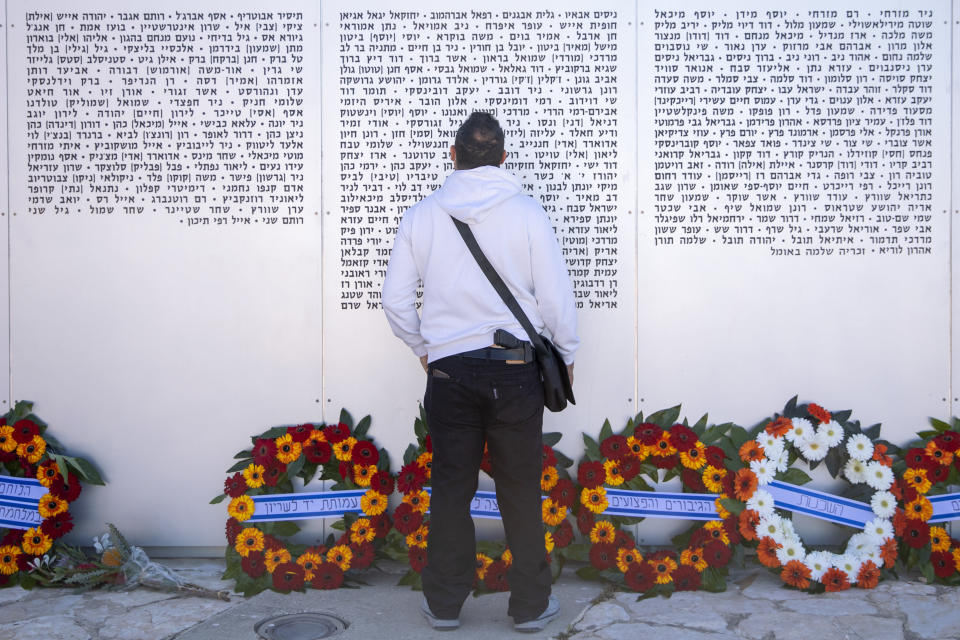 An Israeli man looks for s friend's name on a memorial wall during a ceremony marking the annual Memorial Day to remember fallen soldiers and victims of terror, at the Armored Corps memorial site in Latrun, Israel, Wednesday, April 14, 2021. (AP Photo/Oded Balilty)