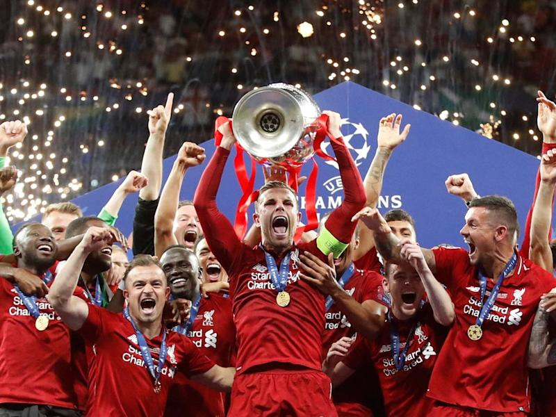 Liverpool's Jordan Henderson celebrates with the trophy: REUTERS