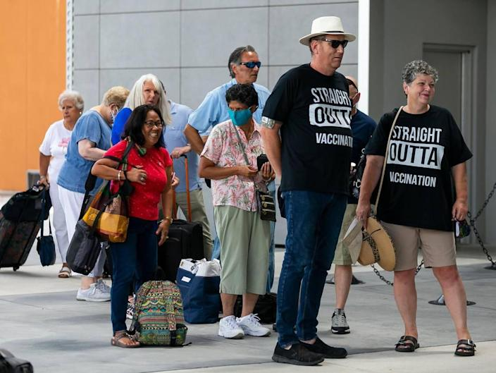 James and Cynthia Mitchell, far-right, from Hope, Kansas, wait in line to board Royal Caribbean's Celebrity Edge cruise ship at Port Everglades Terminal 25 in Fort Lauderdale, Florida on Saturday, June 26, 2021. After departing Port Everglades Saturday, Celebrity Edge will be the first cruise ship sailing with guests from a U.S. port in over 15 months.