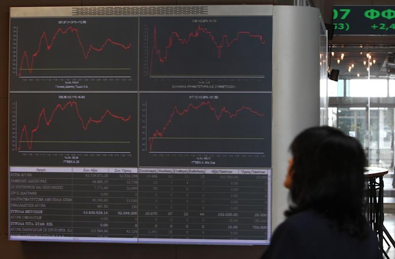 """A woman looks at displays of the Stock Exchange in Athens Tuesday, Oct. 30, 2012. Shares recovered slightly from heavy losses Monday, amid continued uncertainty over a new austerity package due to divisions in the country's coalition government. Conservative Prime Minister Antonis Samaras said Tuesday that the government had essentially ended negotiations on new austerity measures and warned of """"chaos"""" if the reforms are not passed. (AP Photo/Thanassis Stavrakis)"""