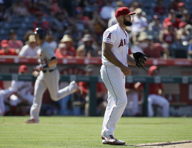 Los Angeles Angels relief pitcher Luis Garcia, right, heads back to the mound as Detroit Tigers' Gordon Beckham runs home after hitting a three-run home run during the eighth inning of a baseball game in Anaheim, Calif., Wednesday, July 31, 2019. (AP Photo/Alex Gallardo)