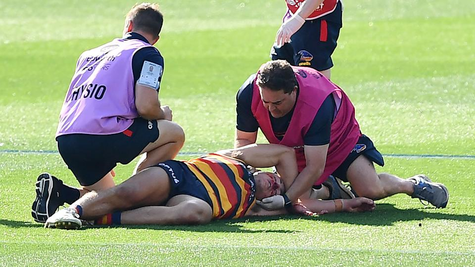 Jake Kelly, pictured here being treated by trainers after his head clash with Patrick Dangerfield.