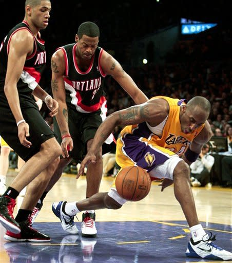 Los Angeles Lakers guard Kobe Bryant, right, dribbles through the lane around Portland Trail Blazers center Marcus Camby, middle, and Trail Blazers forward Nicolas Batum during the first half on an NBA basketball game, Monday, Feb. 20, 2012, in Los Angeles. (AP Photo/Bret Hartman)