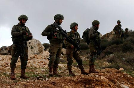 Israeli soldiers stand guard near the scene of a shooting attack near Ramallah in the Israeli-occupied West Bank