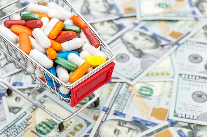A miniature shopping cart filled with pills on top of a pile of hundred dollar bills.