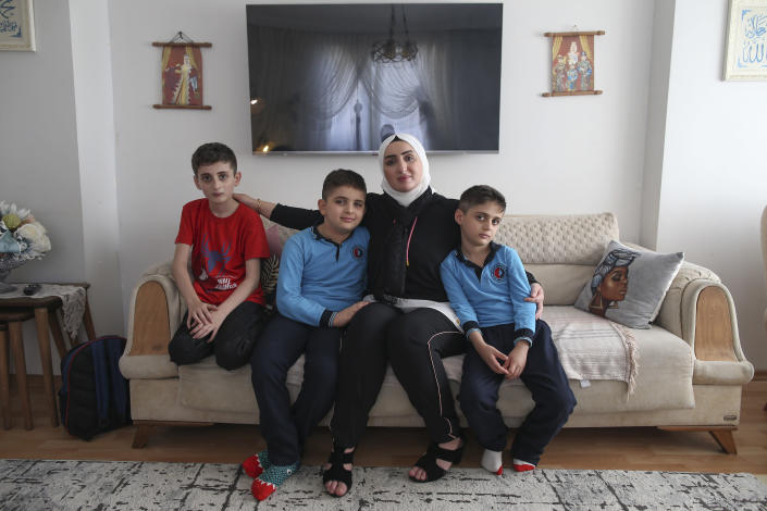 """Fatima Alzahra Shon, 32, a Syrian refugee, poses with her children after an interview with The Associated Press in Istanbul, Friday, Sept. 17, 2021. Shon thinks neighbors attacked her and her son Amr, second left, in their Istanbul apartment building because she is Syrian. The 32-year-old refugee from Aleppo was confronted on Sept. 1 by a Turkish woman who asked her what she was doing in """"our"""" country. Shon replied, """"Who are you to say that to me?"""" The situation quickly escalated. (AP Photo/Emrah Gurel)"""