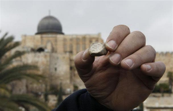 Israel Antiquities Authority (IAA) archaeologist Eli Shukron shows an ancient seal, at an archaeological site known as the City of David in Jerusalem December 25, 2011. Israeli archaeologists said on Sunday they had found the 2,000-year-old clay seal near Jerusalem's Western Wall, confirming written accounts of ritual practices in the biblical Jewish Temple. The Al-Aqsa Mosque, on the compound known to Muslims as al-Haram al-Sharif and to Jews as Temple Mount, is seen in the back.
