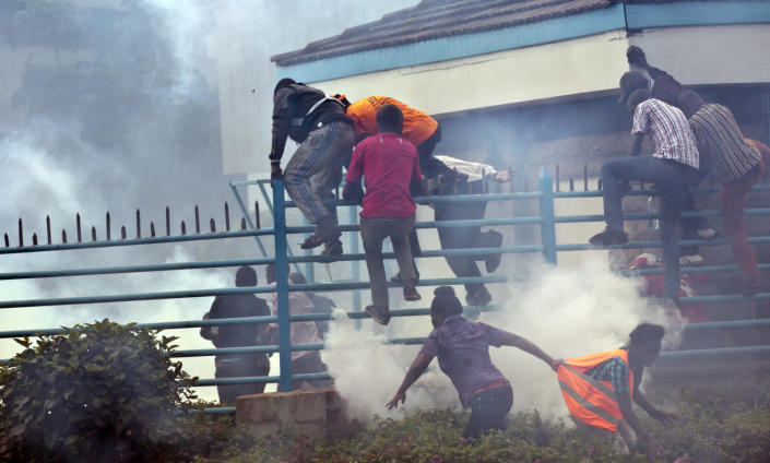 Opposition supporters climb over a fence and into the University of Nairobi campus as they flee from clouds of tear gas fired by riot police during a protest in downtown Nairobi, May 16, 2016. Kenyan police have tear-gassed and beaten opposition supporters during a protest demanding the disbandment of the electoral authority over alleged bias and corruption. (AP Photo/Ben Curtis)