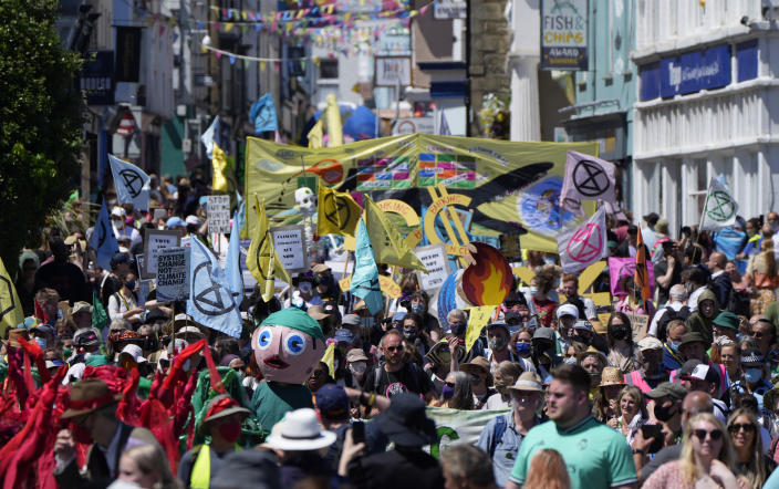 Activists march through the streets with banners and signs during a demonstration around the meeting of the G7 in Falmouth, Cornwall, England, Saturday, June 12, 2021. Leaders of the G7 gather for a second day of meetings on Saturday, in which they will discuss COVID-19, climate, foreign policy and the economy. (AP Photo/Alastair Grant)