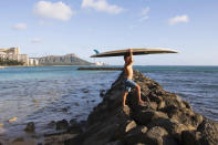 In this photo provided by Yoko Liriano, Bryant de Venecia poses for a photo with his paddleboard in Honolulu, Wednesday, Nov. 11, 2020. He started stand-up paddle-boarding when there were fewer tourists coming to Hawaii during the pandemic. He's among the Hawaii residents feeling ambivalence toward tourists returning now that the state is allowing incoming travelers to to bypass a 14-day quarantine with a negative COVID-19 test. (Yoko Liriano via AP)