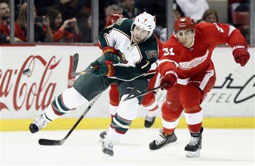 Minnesota Wild center Matt Cullen (7) manages to clear the puck against Detroit Red Wings center Valtteri Filppula (51), of Finland, during the first period of an NHL hockey game, Wednesday, March 20, 2013, in Detroit. (AP Photo/Duane Burleson)