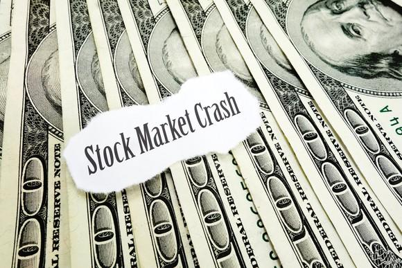 the words stock market crash printed on a torn piece of paper sitting on a bed of hundred dollar bills