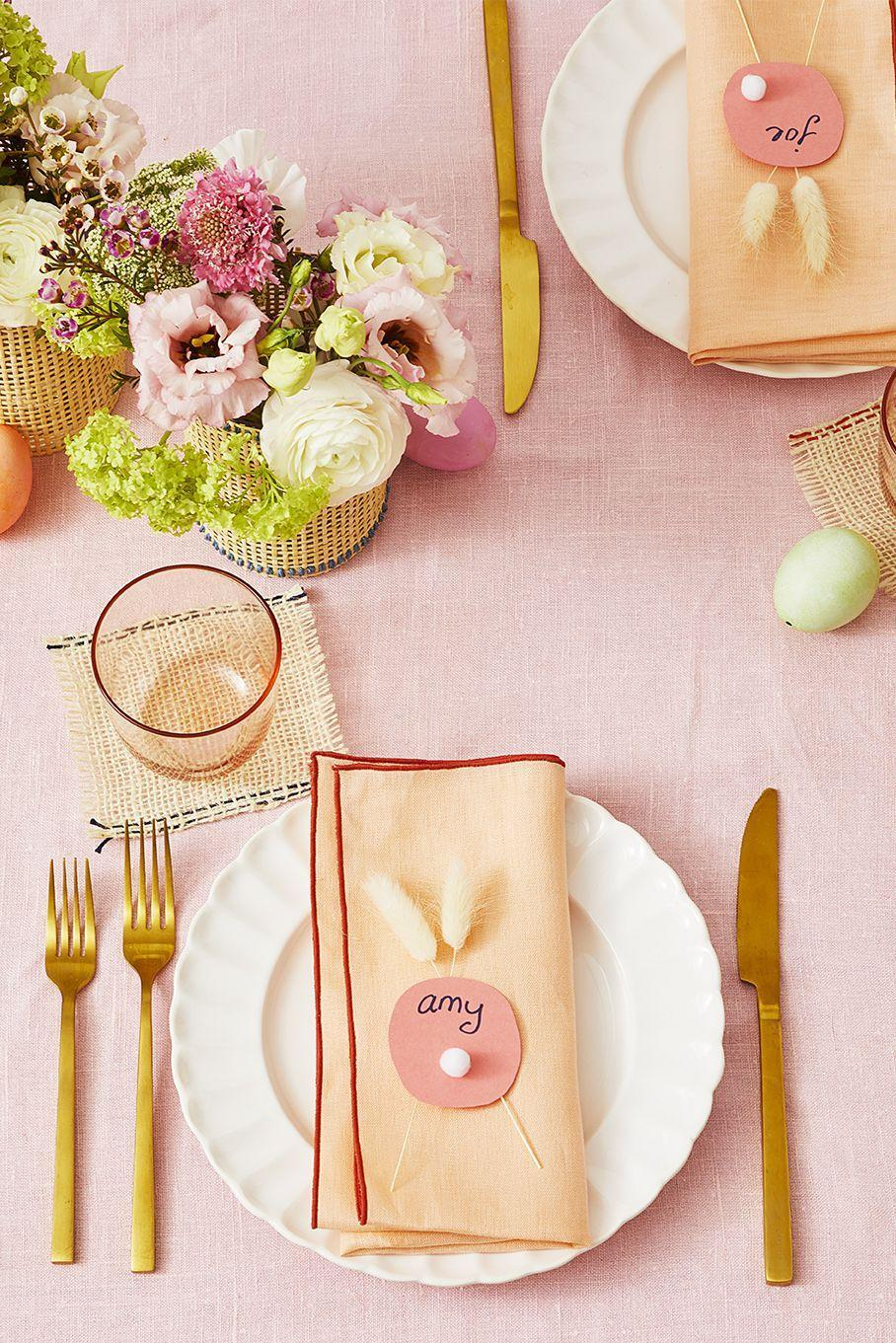 """<p>Make a cardstock circle for each of your guests and glue on a pom-pom bunny tail. Criss-cross two faux flowers to create cute bunny ears. Rose gold silverware and pink linens add a festive spring touch. </p><p><strong>RELATED:</strong> <a href=""""https://www.goodhousekeeping.com/holidays/easter-ideas/g711/easter-spring-crafts/"""" rel=""""nofollow noopener"""" target=""""_blank"""" data-ylk=""""slk:44 Cheerful Easter Crafts That Kids Will Totally Love"""" class=""""link rapid-noclick-resp"""">44 Cheerful Easter Crafts That Kids Will Totally Love</a></p>"""