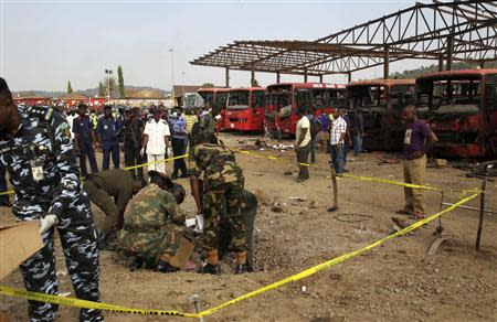 Bomb experts gather evidence in a crater that was caused by a bomb blast explosion in Abuja