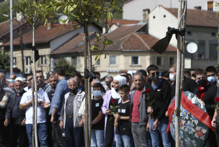 Black ribbons are tied to the trees as people are gathering to honor the victims of the fire in a hospital, in North Macedonia's northwestern town of Tetovo, Saturday, Sept. 11, 2021. Hundreds of people have marched Saturday in northwestern town of Tetovo to honor their 14 countrymen killed in a deadly fire that broke earlier this week and destroyed COVID-19 field hospital. (AP Photo/Boris Grdanoski)
