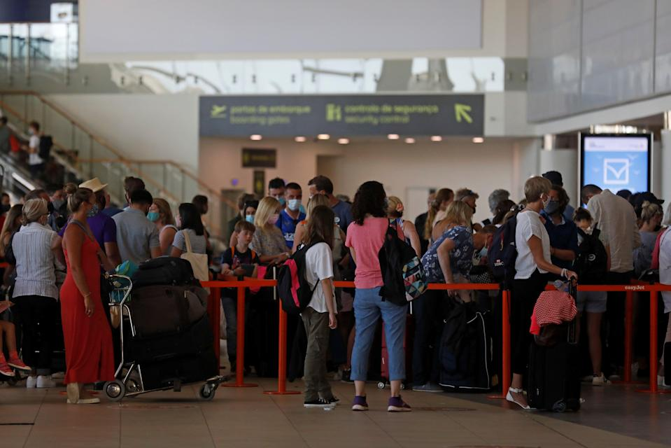 <p>People wait in queues at Faro airport </p> (REUTERS)