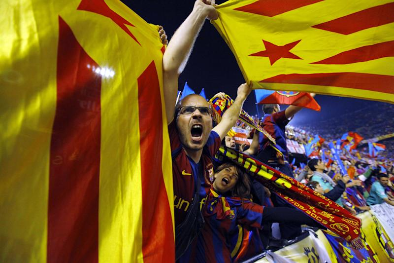 """FILE- In this April 20, 2011, file photo, Barcelona fans wave pro-independence Catalonia flags during the final of the Copa del Rey soccer match between Real Madrid and FC Barcelona at the Mestalla stadium in Valencia, Spain. More than ever, FC Barcelona, known affectionately as Barca, lived up to its motto of being """"more than a club"""" for this wealthy northeastern region where Spain's economic crisis is fueling separatist sentiment. Barca has been seen as a bastion of Catalan identity dating back to the three decades of dictatorship when Catalans could not openly speak, teach or publish in their native Catalan language. Barcelona writer Manuel Vazquez Montalban famously called the football team """"Catalonia's unarmed symbolic army."""" (AP Photo/Andres Kudacki, File)"""