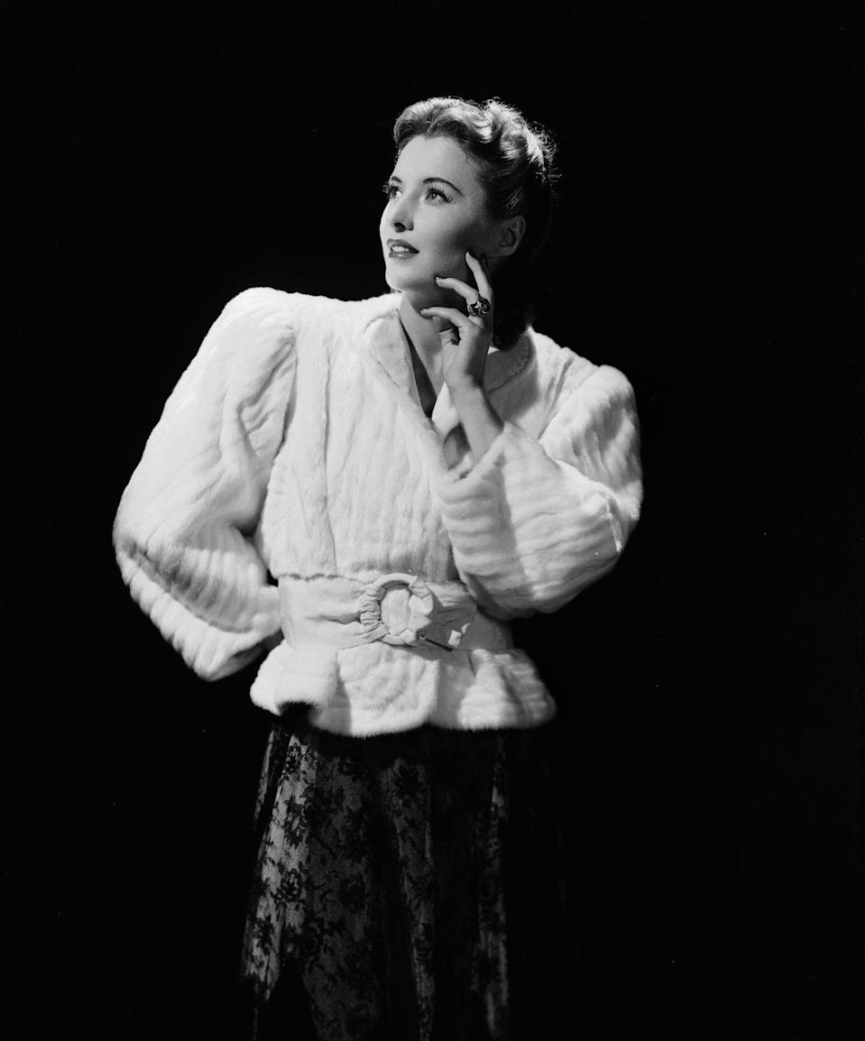 <p>Barbara Stanwyck wears a white mink ribbed jacket with linebacker shoulders over a lace skirt.</p>