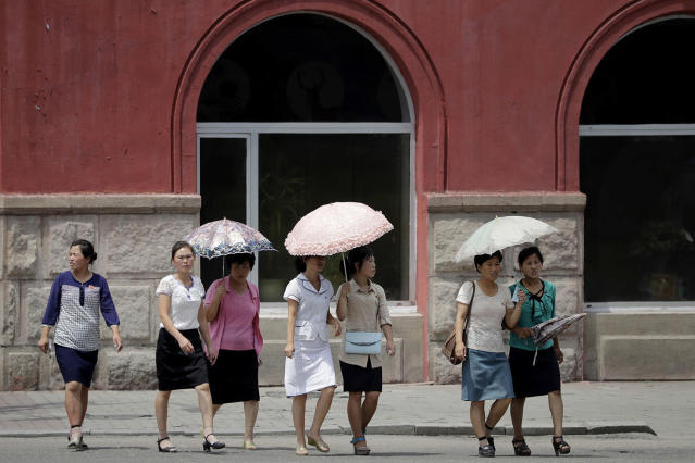 <p>Women carry parasols as they walk down the street of downtown Pyongyang on July 26, 2017, North Korea. (Photo: Wong Maye-E/AP) </p>