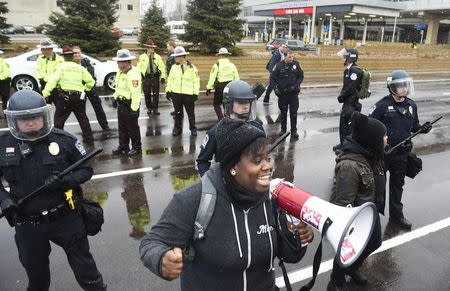 A protester named Oluchi of Minneapolis speaks to protesters after they shut down the main road to the Minneapolis St. Paul Airport following a short protest at the Mall of America in Bloomington, Minnesota December 23, 2015. REUTERS/Craig Lassig