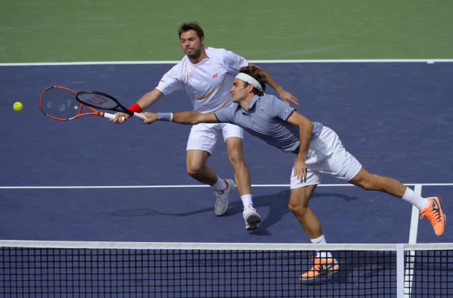 Roger Federer, of Switzerland, right, stretches for the ball as doubles partner Stanislas Wawrinka, of Switzerland, looks on during a match at the BNP Paribas Open tennis tournament against Rohan Bopanna, of India, and Aisam-Ul-Haq Qureshi, of Pakistan, Friday, March 7, 2014 in Indian Wells, Calif. (AP Photo/Mark J. Terrill)