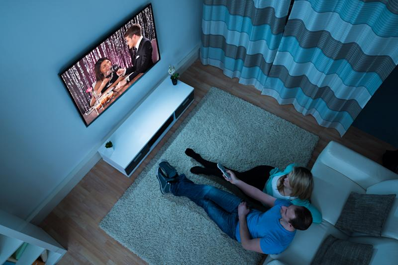 Couple watching TV in a darkened living room.