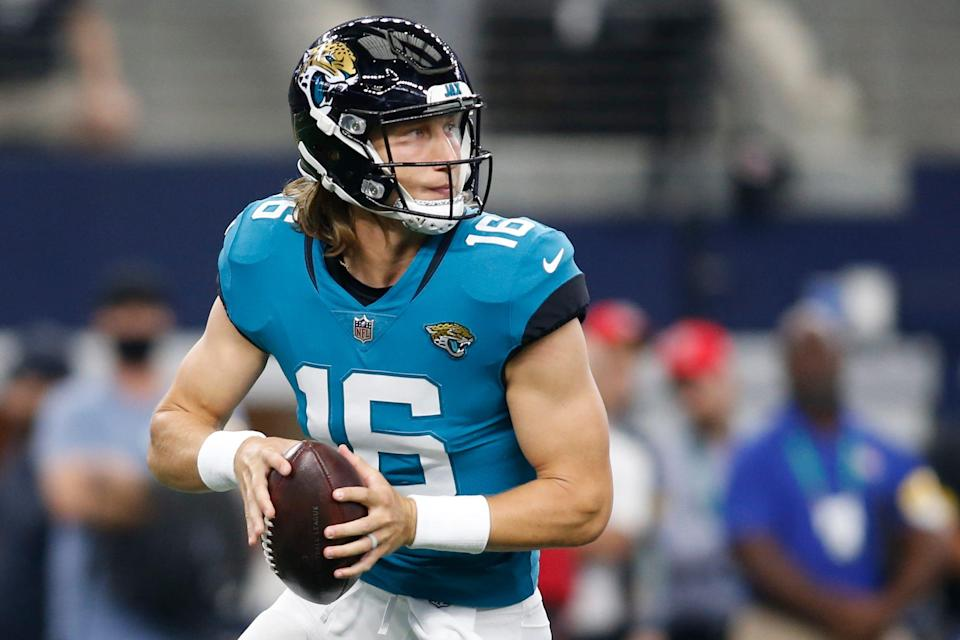 Jacksonville Jaguars quarterback Trevor Lawrence (16) rolls out to throw a pass in the first quarter against the Dallas Cowboys at AT&T Stadium.
