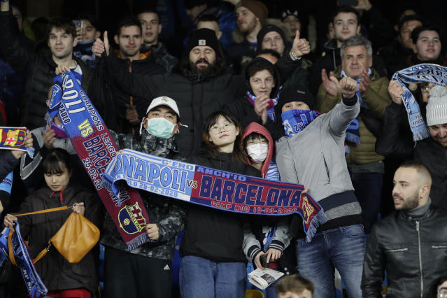 Soccer fans wait for the start of the Champions League, Round of 16, first-leg soccer match between Napoli and Barcelona, at the San Paolo Stadium in Naples, Italy, Tuesday, Feb. 25, 2020. (AP Photo/Andrew Medichini)