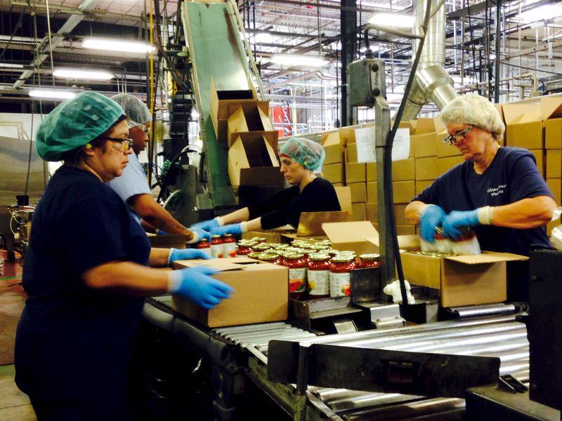 Workers box jars of pasta sauce at a plant run by Chelten House Products in Bridgeport, New Jersey