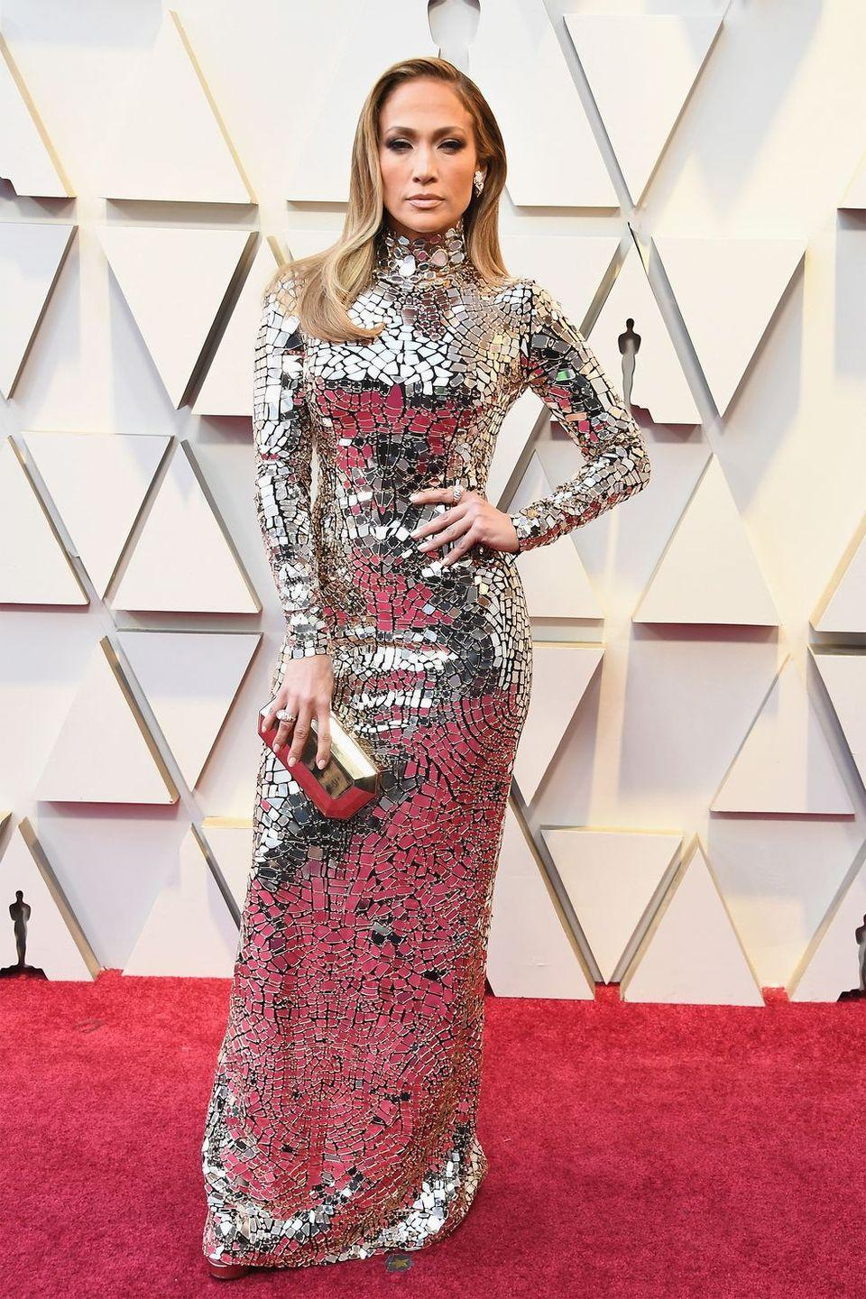 """<p>We bow down to this <a href=""""https://www.harpersbazaar.com/celebrity/red-carpet-dresses/a23119249/jennifer-lopez-oscars-kim-kardashian-met-gala/"""" rel=""""nofollow noopener"""" target=""""_blank"""" data-ylk=""""slk:disco ball of a human"""" class=""""link rapid-noclick-resp"""">disco ball of a human</a>, in a metallic embroidered mirror mosaic long-sleeved gown by Tom Ford. It's all glamour for the most glam night of the year.</p>"""