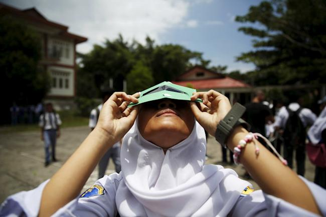 A student tests a self-made filter and looks at the sun after a joint workshop between the Hong Kong Astronomical Society and Indonesia's National Institute of Aeronautics and Space (LAPAN) at a high school in Ternate island, Indonesia, ahead of Wednesday's solar eclipse, March 7, 2016. REUTERS/Beawiharta