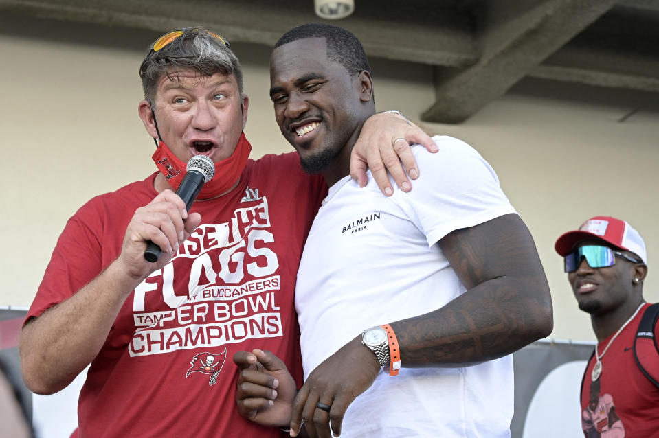 FILE - Tampa Bay Buccaneers general manager Jason Licht, left, address the audience with linebackers Lavonte David, center, and Devin White during a celebration of their Super Bowl 55 victory over the Kansas City Chiefs in Tampa, Fla., in this Wednesday, Feb. 10, 2021, file photo. When Jason Licht declared he was going to do everything he could to keep the Tampa Bay Buccaneers together, no one envisioned the process going as smoothly as it has for the Super Bowl champions. (AP Photo/Phelan M. Ebenhack, File)