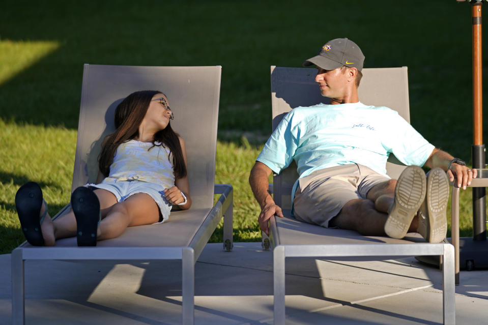 Cecilia Shaffette relaxes in the backyard with her father Rhett Shaffette, at their home in Carriere, Miss., Wednesday, June 16, 2021. The 12-year-old is thriving, eight months after getting a portion of her father's liver. She received the transplant after nearly losing her life to internal bleeding. (AP Photo/Gerald Herbert)