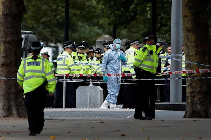 Police and forensic officers gather in the road near the Natural History Museum (REUTERS)