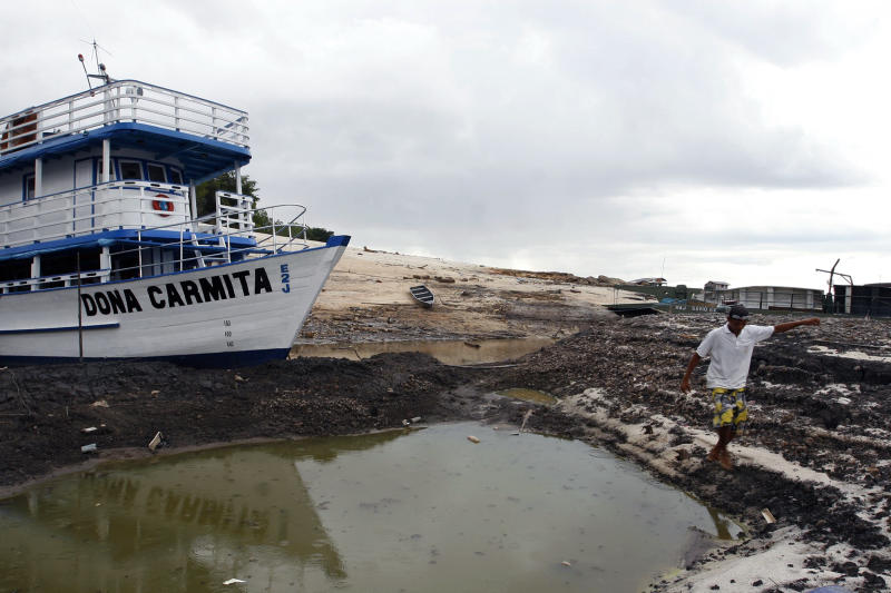A man walks past a boat sitting at the dry Rio Negro river in Manaus, Brazil, Sunday, Oct. 24, 2010. The Rio Negro river, one of the Amazon river's largest tributaries, registered historic draught levels this weekend, which could affect thousands of fishing communities in the region. According to Brazilian civil defense officials, the depth of the Black river dropped by six centimeters. (AP Photo/Bruno Kelly)