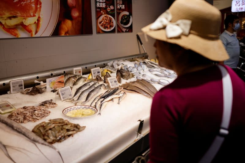 A woman looks at seafood at a supermarket in Shanghai