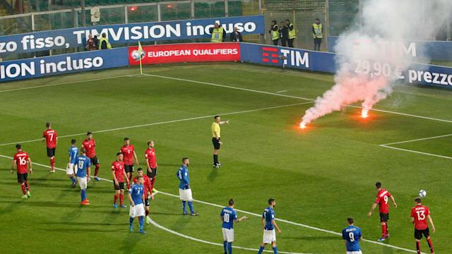 Albania fans caused a delay to their World Cup qualifier with Italy by throwing flares onto the pitch and FIFA has issued a fine.