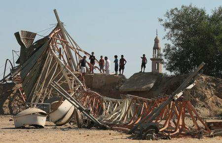 Palestinians look at damage at a training camp belonging to the Islamist group Hamas after it was hit by an Israeli air strike in the northern Gaza Strip September 19, 2015. REUTERS/Mohammed Salem