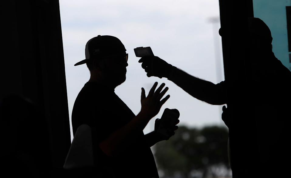 Amid concerns of the spread of the virus that causes COVID-19, a baseball fan has his temperature checked by a security guard before being allowed to tour Globe Life Field, home of the Texas Rangers baseball team in Arlington, Texas, Monday, June 1, 2020. (AP Photo/LM Otero, File)