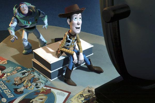 Buzz Lightyear (voiced by Tim Allen) watches Woody (voiced by Tom Hanks) watching TV.
