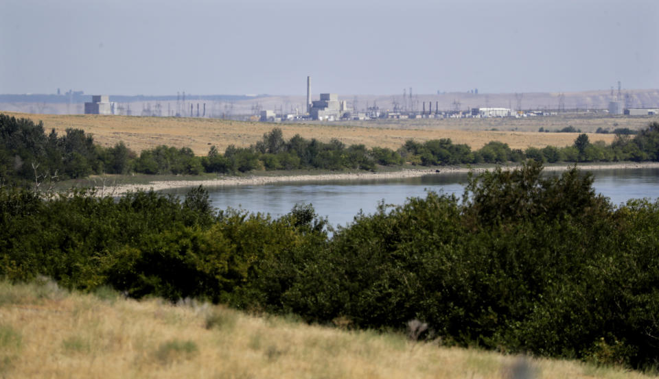 FILE - In this Aug. 14, 2019 photo, buildings on the Hanford Nuclear Reservation along the Columbia River are seen from the Hanford Reach National Monument near Richland, Wash. The location is featured in a collection of mini-essays by American writers published online by the Frommer's guidebook company about places they believe helped shape and define America. (AP Photo/Elaine Thompson, File)