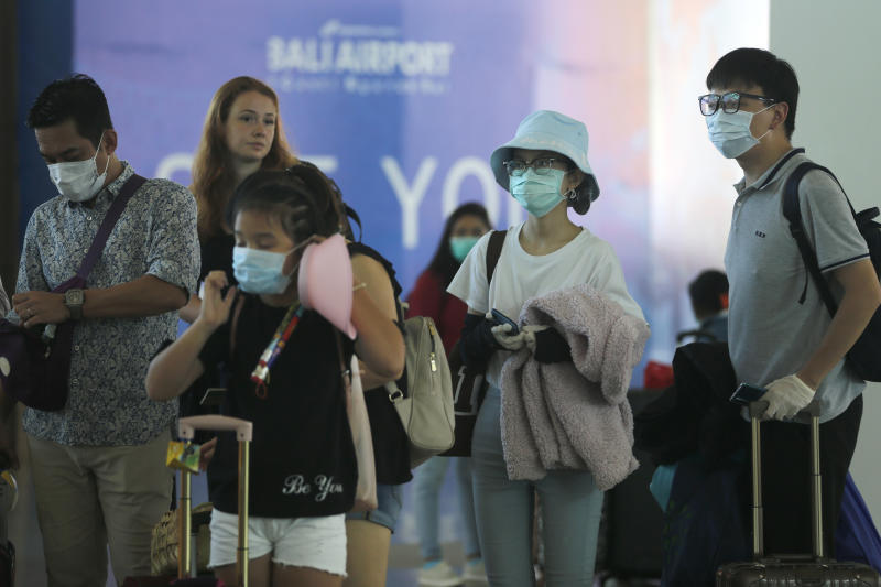 Tourists wearing face masks line up to a departure gate at Bali airport, Indonesia, Saturday, Feb. 8, 2020. Thousands of Chinese tourists are reportedly stranded in Bali following suspending all flights to and from China amid growing concerns about the coronavirus outbreak. (AP Photo/Firdia Lisnawati)