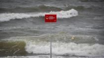 A danger sign is seen as the surf surges on the beach ahead of Tropical Storm Isaias in the Rockaway area of Queens in New York