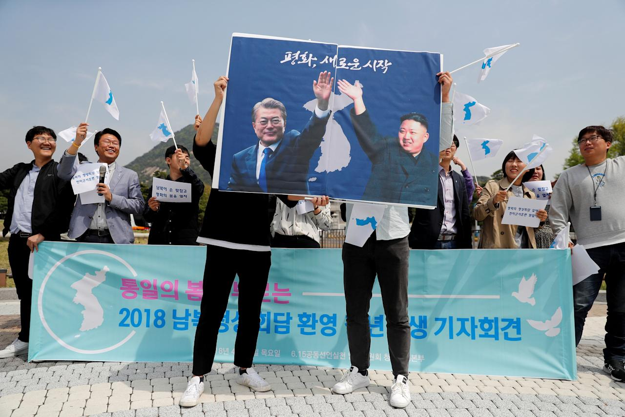 Students hold posters with pictures of South Korea's President Moon Jae-in and North Korea's leader Kim Jong Un during a pro-unification rally ahead of the upcoming summit between North and South Korea in Seoul, South Korea April 26, 2018. REUTERS/Jorge Silva     TPX IMAGES OF THE DAY