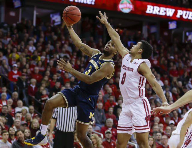 """Michigan's <a class=""""link rapid-noclick-resp"""" href=""""/ncaab/players/136106/"""" data-ylk=""""slk:Zavier Simpson"""">Zavier Simpson</a> (3) shoots against Wisconsin's D'Mitrik Trice (0) on Saturday in Madison, Wis. (AP)"""