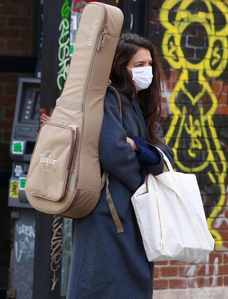 <p>Katie Holmes is almost unrecognizable while toting her guitar through N.Y.C.'s SoHo neighborhood on Tuesday.</p>