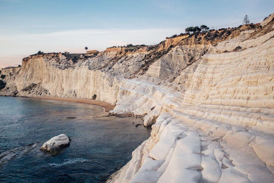 """<p>With a name that translates to """"<a href=""""https://www.svadore.com/1-must-see-beach-sicily-scala-dei-turchi/"""" rel=""""nofollow noopener"""" target=""""_blank"""" data-ylk=""""slk:Turkish Steps"""" class=""""link rapid-noclick-resp"""">Turkish Steps</a>,"""" you may not be surprised to see a grand staircase leading to the Mediterranean Sea. The white limestone background, <a href=""""http://www.visitsicily.info/en/scala-dei-turchi/"""" rel=""""nofollow noopener"""" target=""""_blank"""" data-ylk=""""slk:sculpted"""" class=""""link rapid-noclick-resp"""">sculpted</a> by swirling winds, is a striking Sicilian sight.</p>"""