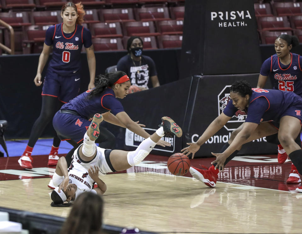South Carolina guard Zia Cooke (1) falls as Mississippi guard Donnetta Johnson (3) and forward Iyanla Kitchens (32) go for a loose ball during the first half of an NCAA college basketball game in Columbia, S.C., Thursday, Feb. 25, 2021. (Tracy Glantz/The State via AP)