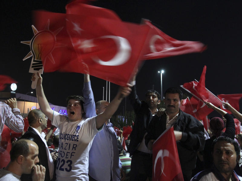 Supporters of Turkish Prime Minister Recep Tayyip Erdogan chant slogans upon his arrival at the Ataturk Airport of Istanbul early Friday, June 7, 2013. Erdogan took a combative stance on his closely watched return to the country early Friday, telling supporters who thronged to greet him that the protests that have swept the country must come to an end. In the first extensive public show of support since anti-government protests erupted last week, more than 10,000 supporters cheered Erdogan with rapturous applause outside Istanbul's international airport. (AP Photo/Thanassis Stavrakis)