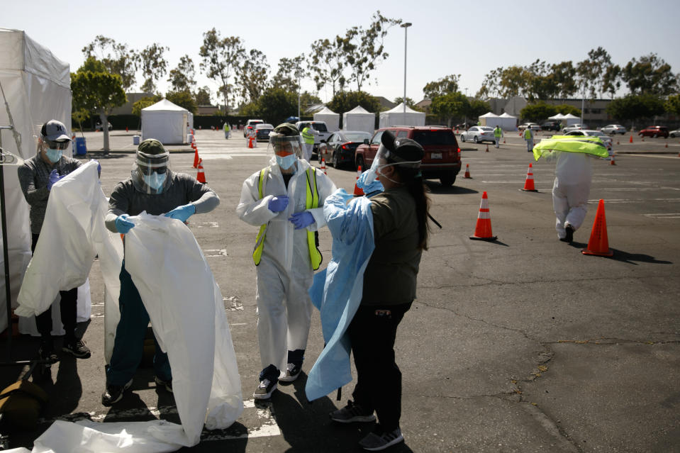 A group of volunteers put on protective suits at a city-run, drive-thru COVID-19 testing site in South Central Los Angeles, Friday, May 22, 2020. While most of California is welcoming a slight return toward normal this holiday weekend, Los Angeles will not be joining the party. The nation's largest county is not planning to reopen more widely until the next summer holiday, July 4th, because of a disproportionately large share of the state's coronavirus cases and deaths that have hampered the county's ability to rebound and meet strict criteria to get more people back to work. (AP Photo/Jae C. Hong)